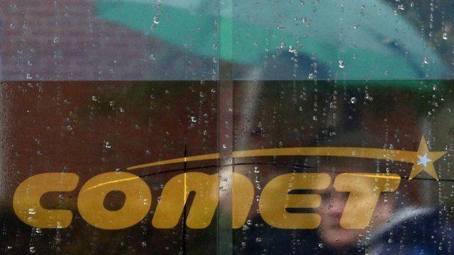 Shoppers reflected in Comet window