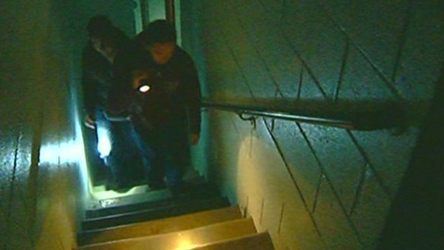 Men walking up tower block stairs by torchlight