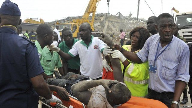 Rescue workers carry an injured man out from the debris of a collapsed building in Ghana's capital, Accra - Wednesday 7 November 2012
