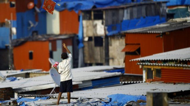An Indian boy tries to fly a kite from a roof top in a slum neighborhood of Mumbai