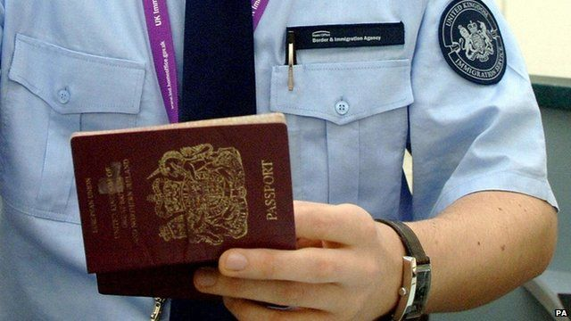 Immigration officer checking a passport at Heathrow Airport