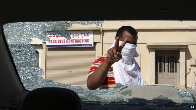 Man inspects damage to a car in Bahrain