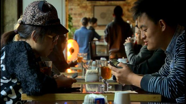 Two young people in China using mobile phones
