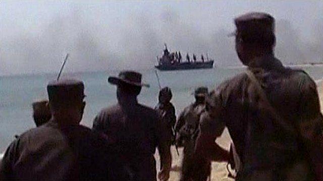 Sri Lankan military looking towards smoke from a battle