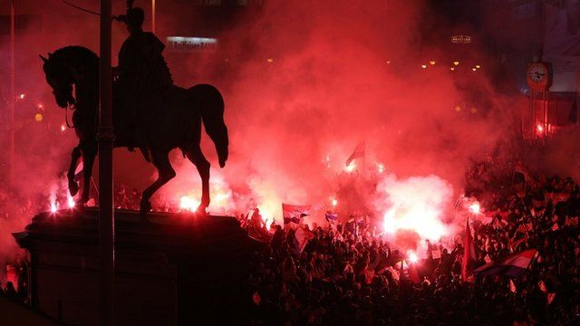 People light red flares during a rally held in honour of the two former generals