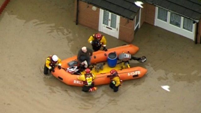Aerial shot of man being rescued from his flooded house by dinghy