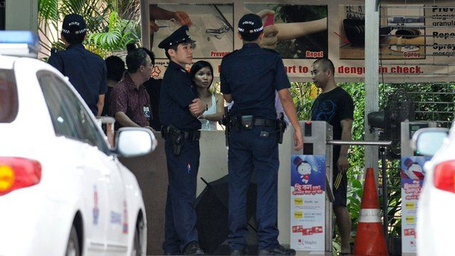 Policemen stand by the entrance to a foreign workers dormitory in Singapore on November 26, 2012