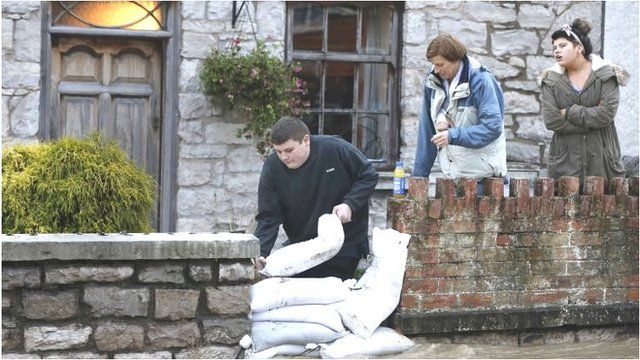 A man adds sandbags to a flood defence in an attempt to stop floodwaters entering a home in St Asaph, north Wales