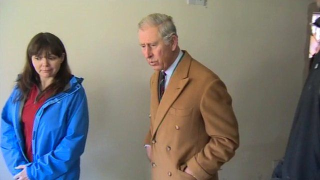 Prince Charles in a flooded house standing beside the owner