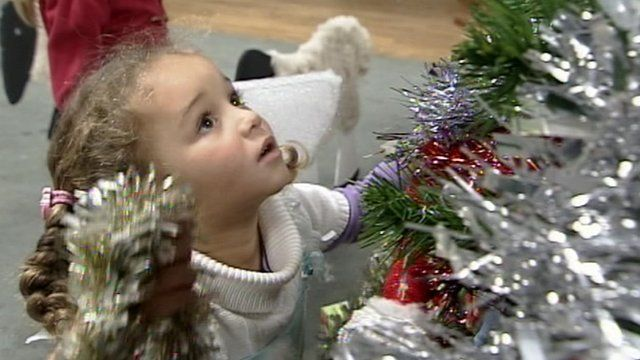 A girl helps decorate a Christmas tree with tinsel