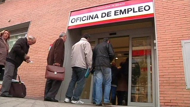 Unemployed people queue to get into a job centre in Spain