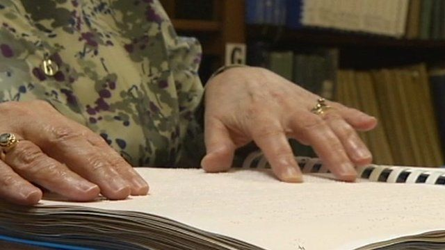 Woman reads braille book