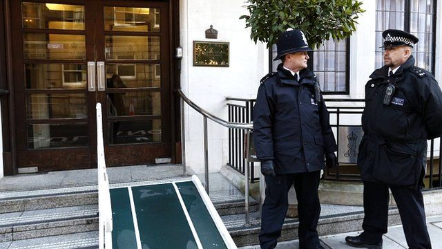 Police officers stand outside King Edward VII hospital in London