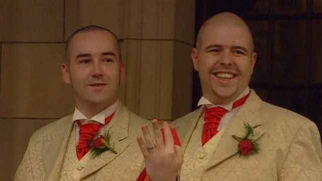 Male same-sex couple showing off wedding ring