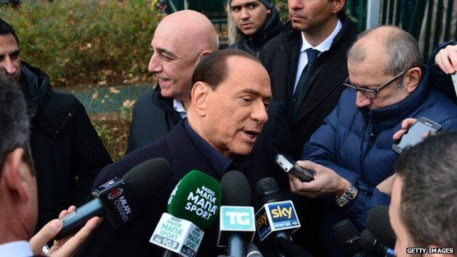 Silvio Berlusconi surrounded by reporters