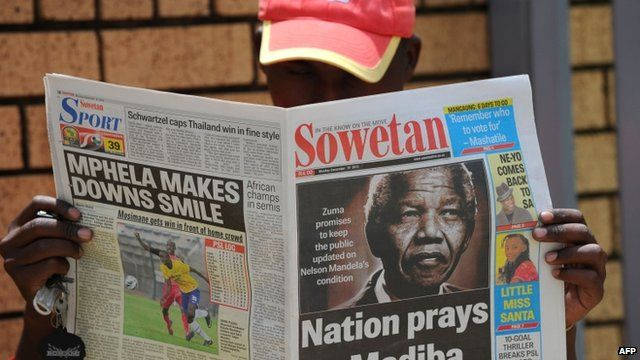Man reads newspaper with story about Nelson Mandela in hospital