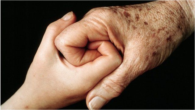 Old and young person holding hands