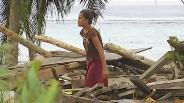 Woman standing in middle of debris made of remains of wooden building