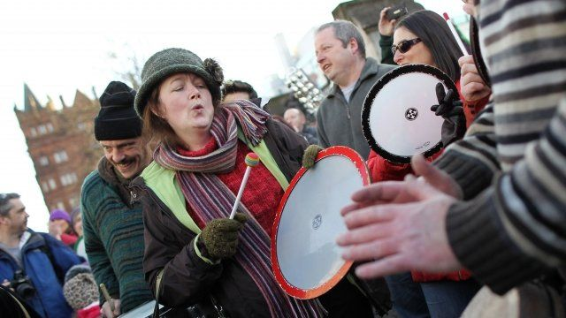 Demonstrators play percussion instruments as up to 1,000 people gather to take part in a peace rally outside Belfast City Hall in Belfast
