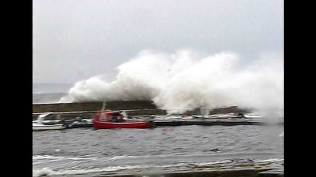 Waves crash over a harbour wall