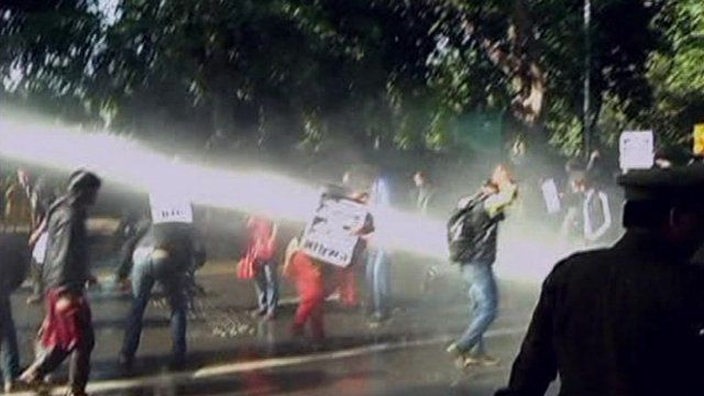 Protesters carrying placards being hosed by Delhi police