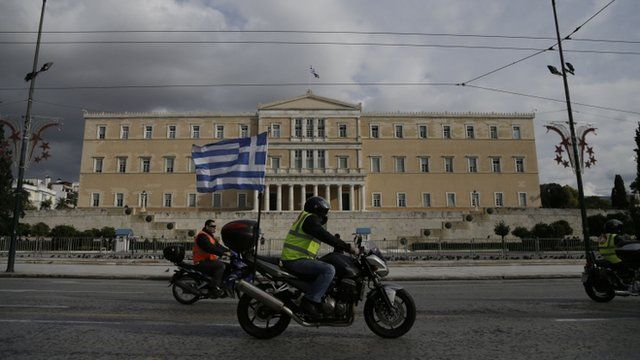 Motorcycles and a Greek flag pass in front of Greek parliament