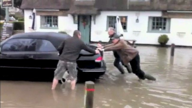Men push car out of floodwater in Elsworth, Cambridgeshire