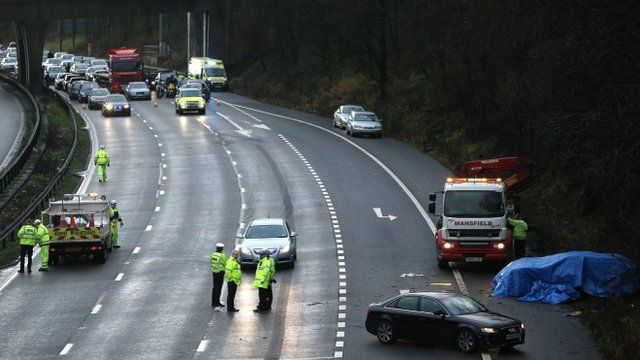 Emergency workers at the scene of the M6 crash, with traffic tailing back behind them