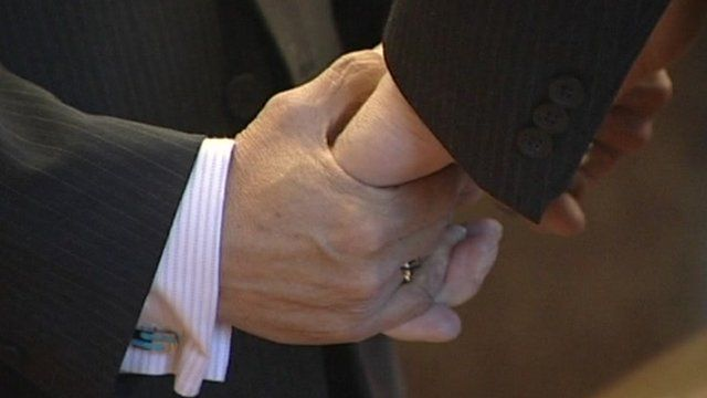 Men holding hands during a wedding ceremony