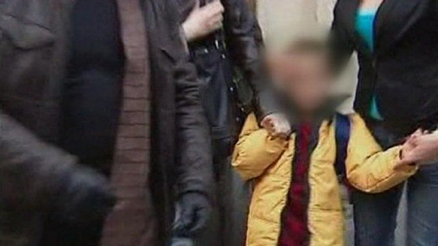 Child with face blurred is led away by adults in Russia