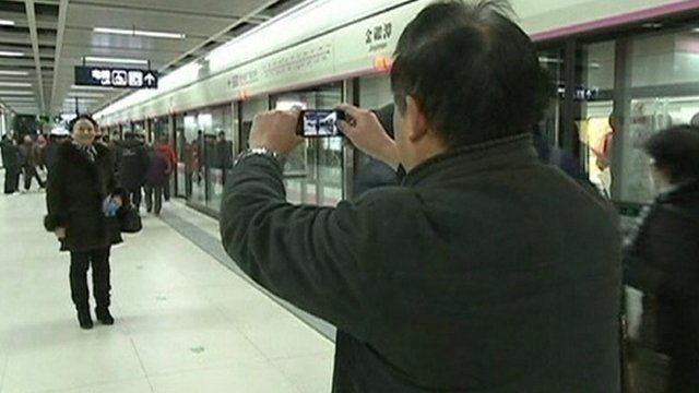 Passengers pose for pictures on the new subway line