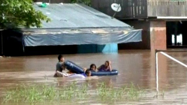 People in dinghy in flooded street