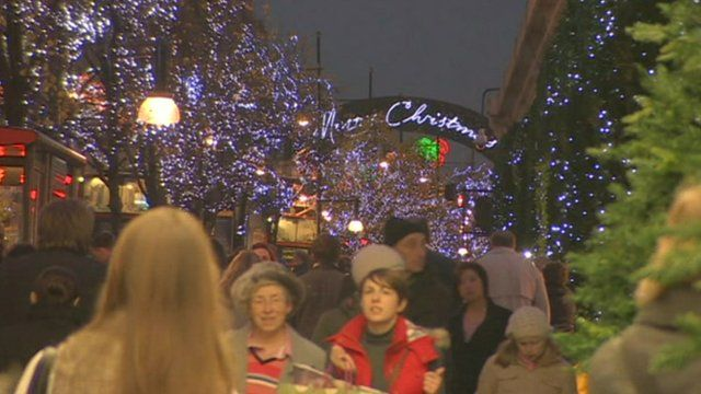 Shoppers on street with Christmas lights