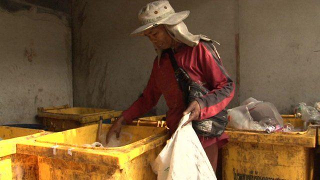 A man rummages through a bin in Bangkok