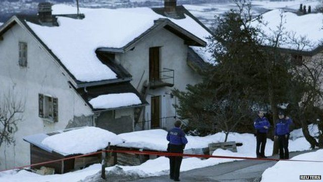 Three police officers stand near the cordoned-off crime scene (3 January 2012)
