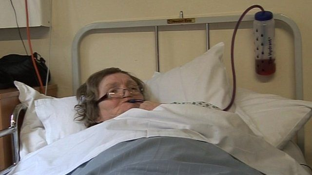 Patient in hospital bed drinking from a long straw out of a water bottle