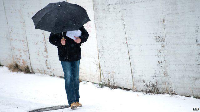 man walks under an umbrella