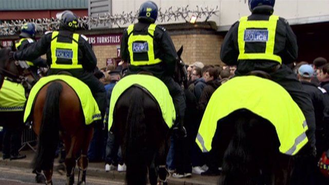 Police officers on horses outside a football match