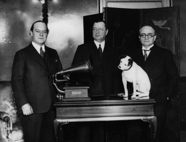 HMV dog listening to a gramophone while bosses look on