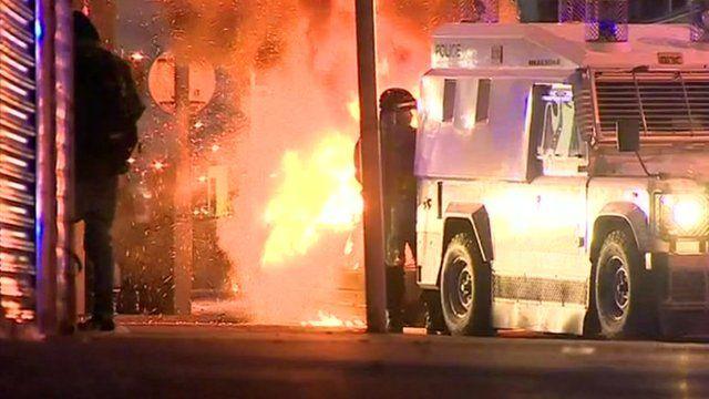 Fire burns near a police vehicle