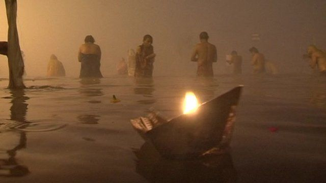 People and candle in water at Sangam