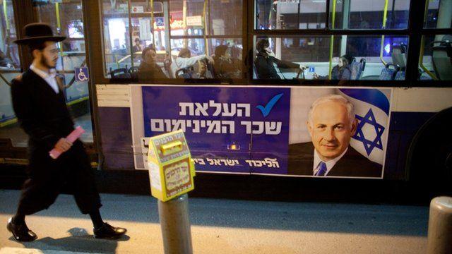 People walk past Netanyahu poster