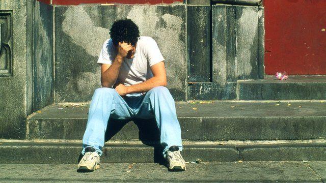 Teenage boy sits on stone steps