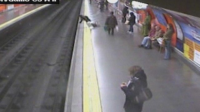 A woman falls from a train platform onto the tracks