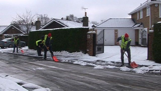 Three men with spades clearing snow from a residential street