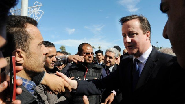 UK Prime Minister David Cameron meeting Libyans, flanked by security guards