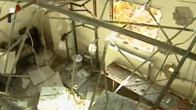 Still image from Syria state TV footage showing damage to room