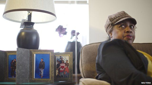 Shirley Chambers sitting by photos of her children in her home
