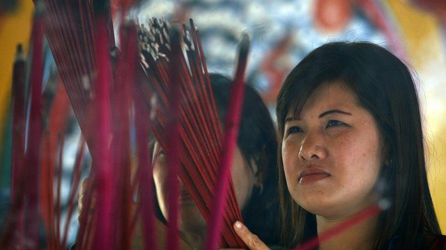 An Indonesian ethnic Chinese woman holds incense sticks during Lunar New Year celebrations at a temple in Jakarta, Indonesia