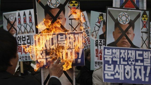An activist from an anti-North Korea civic group burns a portrait of North's leader Kim Jong-un during a rally against North Korea's nuclear test near the U.S. embassy in central Seoul.